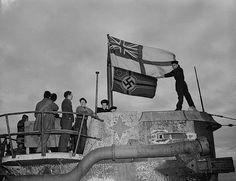 Seamen raise the White Ensign (Britain's naval flag) over the captured German U-boat U-190 in St. John's, Newfoundland 1945.