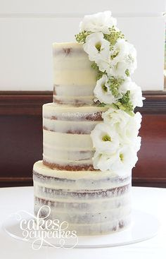 semi naked cake, thin icing w/ cascading flower decoration   flowers:  ranunculus + green beads