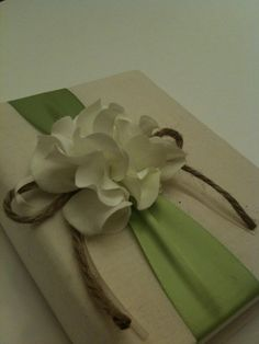 Rustic photo album- Accented with a cluster of lovely white hydrangeas affixed to a wide pale green ribbon, tied with a rustic ivory ribbon and rope bow.