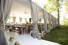 tent + grey curtains + wood benches + white flooring // wedding reception inspiration