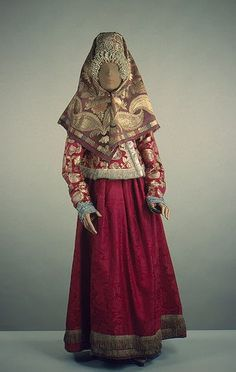"Russian traditional costume probably from Novgorod region. Headdress ""kika"" with pearls decoration over forehead (ochel`ye), head shawl, dushegreya-shugay (warm jacket) and sarafan (dress):"