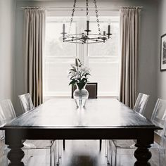 Lucite dining room chairs with a heavy looking table makes the small space not look as crowded.
