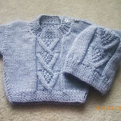 """This little sweater features a double moss-filled cross-over chevron at the centre of the front and back. This makes a lighter sweater than a full aran, and gives you enough detail to work with if you are new to the cable needle. Make it in a neutral for every-day play, or pastel or stained-glass colours with fancier buttons for a dressed-up look. The chevron pattern is also featured on the roomy hat. Ardan is pronounced """"are-dawn"""" and means """"high aspiration."""""""