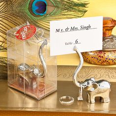 """Your guests will be lucky to receive these Majestic Elephant Place Card Holders as double duty wedding favors! Trunk lifted high in the air, the elephant is a beloved symbol of abundant blessings and good luck. Each features an extra long trunk to double as a jewelry holder and keep even the most precious wedding bands safe! Who would have """"trunk"""" it"""