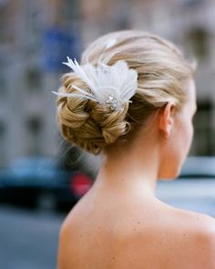 A feather in the hair. Tasteful small and white... Carrie Bradshaw could learn a thing from this bride