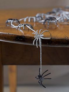 String Up Spooky Spiders -  With a small brush, apply Elmer's glue on the top side of each plastic spider, then shake on black or silver glitter to cover spider (plan to use 4 spiders per foot of garland). When the glue's dried, flip over the spiders and glitter their undersides. When spiders are dry, glue them to a silver cord using a hot-glue gun, spacing them about 3 inches apart. #Halloween #DIY