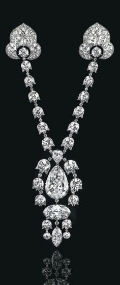 CARTIER - A BELLE EPOQUE DIAMOND DEVANT-DE-CORSAGE BROOCH, CIRCA 1912. The pendant centring upon a pear-shaped diamond, weighing apprx. 34.08 carats, an oval-shaped diamond, and a marquise-shaped diamond, enhanced by Lily-of-the-valley links set with circular-cut diamonds, and suspended from two detachable similarly-set lines, each with a pavé-set old-cut diamond palmette terminal, mounted in platinum, with maker's mark for Henri Picq workshop, signed Cartier. #BelleÉpoque #Cartier #Corsage