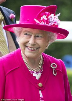 All smiles: The Queen was on cheerful form and accessorised her cerise ensemble with a rub...