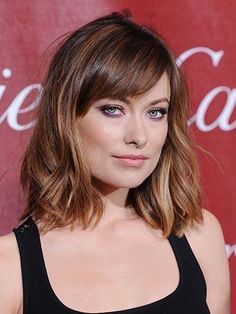 Olivia Wilde sporting a wavy, long bob haircut with side-swept bangs and ombre highlights with purple eyeshadow and pink lips | allure.com