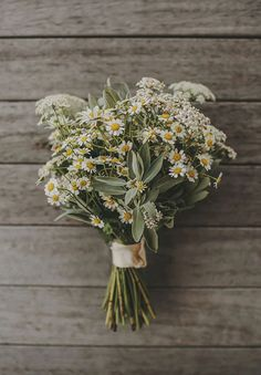 Delicate daisies paired with sage makes a cute and affordable arrangement for a rustic or vintage celebration.