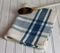 """The fruit of my loom! Pretty kitchen tea towel in colonial blue and natural twill. My """"farmhouse plaid"""" design creates halftone shades of the blue in the fabric. 100% unmercerized cotton yarn is absorbent, which is practical for kitchen towels. Measures approximately 16"""" wide by 22"""" long. Machine stitched hemmed ends make for clean edges. The towel has been prewashed, machine dried and pressed."""