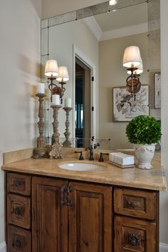 Tuscan Style Bathroom, Old World Feel, Antiqued Mirror, Travertine, Rustic Hardware, Mirror Mounted Sconces  Photography By: Miro Dvorscak