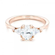 #102473 This stunning engagement ring features an oval cut diamond in the middle, with trillion shaped side stones, all in a rose gold band. It was created...