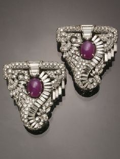 Pair of Art Deco Tested Platinum, Star Ruby and Diamond Dress Clips, Circa 1930. Each triangular reticulated mount set with one oval cabochon ruby, surrounded by twenty-six straight baguette diamonds, one half-moon diamond, one hundred twenty-one round old European-cut diamonds and ten marquise-cut diamonds. #ArtDeco #clip #brooch