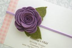 Handmade purple felt flower with green leaves, attached to skinny elastic headband