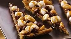 Rocky Road Cookie Pizza made with Pilsbury chocolate chip cookie dough, peanuts, chocolate chips, miniature marshmallows and caramel topping.  So so easy.  Children would love putting this together.