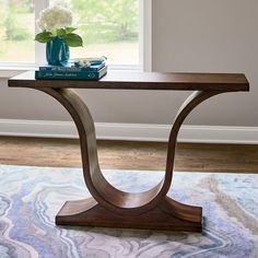 When you want a piece with a little more presence for a formal entryway, a classic living room, or art-filled hall, our exclusive Harp Console is worth a second and third look. The way we've designed it, it offers the sort of lyrical design that you might find in a custom-designed creation, We brought the traditional harp-style base inspiration forward and made it fresh and current with sleeker modern lines. This striking console is crafted for us of solid mindi wood...