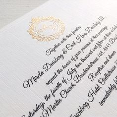 Gold logo embossed wedding invitation in white