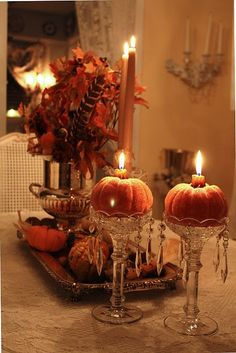pumpkins in glass bowl/candlesticks with small hole cored out for candles...