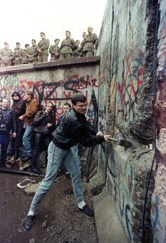 A demonstrator pounds away at the Berlin Wall as East Berlin border guards look on from above the Brandenburg Gate in Berlin in November, 1989 - by David Brauchli, USA/Czech Ap World History, History Photos, Fall Of Berlin Wall, Fernanda Yamamoto, Berlin Hauptstadt, Art Mur, Brandenburg Gate, Paris Match, Reportage Photo