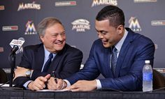 Pictures from the week in sports. Show me the contract !!!  Miami Marlins right fielder Giancarlo Stanton (right) signs his contract next to Marlins owner Jeffery Loria (left) during a press conference at Marlins Park.
