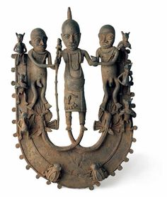 U-Shaped Relief Plaque with Oba and Attendant. Benin, Nigeria. 17th century Bronze. The focal point of this unusual U-shaped relief is an Oba (king of Benin) supported by two attendants, or enobore. Presumably, the elongation of the Oba's legs in the form of hingemouth fish (cf. Fagg, 1963) is meant to emphasize his divinity.