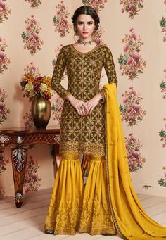 Olive And Yellow Embroidered Gharara Palazzo Suit features a beautiful designer georgette top with delicate traditional embroidery with zari and resham machine work that goes amazingly with the hues of the dress.