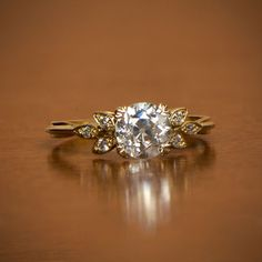 A delicate and stunning vintage style engagement ring centering a 1.07 carat old European cut J color, and VS1 clarity diamond. Flanking the center stone is leaves set with an old cut diamond. The shank of this ring is triple wire. This ring is entirely hand-crafted in 18k yellow gold. An picture of this ring on a finger is available upon questions.  If you have any questions about this ring, please feel free to contact us.