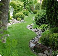 River rock beds along the garden path - gives the sense of edging but more casual and flows curves like a river