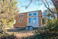The tiny house has a floor space of 8 x 20 ft (2.4 by 6 m) and features an elevated loft h...