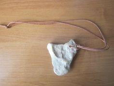 """""""Neolityczny"""" naszyjnik z kamienia. Ręcznej roboty naszyjnik z rzecznego kamienia utrzymany w stylu, który można określić jako neolityczny. Wykonany ze zwyczajnego rzecznego kamienia o niebanalnym kształcie. Unikatowy kształt wisiorka. Każdy mój wisiorek jest inny. Otwór wykonany ręcznie. Długość 7 cm, szerokość 5 cm, grubość 0,5 cm."""