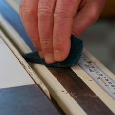Apply a coating of paste wax to all of the surfaces including the table, miter gauge, fence and the fence guide strip. Polish the surface with a cloth.