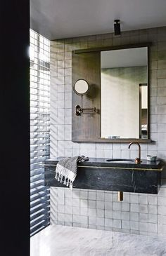 In the main ensuite, Parisi 'Twinset 430' undercounter basin set in Nero Marquina marble from CDK Stone; Icon aged brass mixer from Astra Walker; Perrin & Rowe shaving mirror from The English Tapware Company; 'Zanzibar 300-32' mosaic tile in Grey Matt from Signorino.