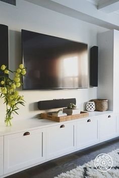 white built-in with shaker style cabinets under the wall mounted tv. This TV room has some serious surround sound! Decorate a media console with a tray and home decor. A tray is perfect for displaying accessories in because you can move it in a pinch AND use it to serve guests.