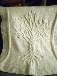 """She used Sirdar Denim Chunky and kind of made the pattern up as she went. Freeform cables are fun, although she thinks one side of the tree is a bit bushier than the other! The leaves are knitted separately and sewn on. Finished size is about 30x36""""."""