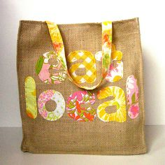 This links only to the photo, but it should be easy enough to find a tote pattern on Pinterest and add any letters you want. This one used letters cut out of old sheets.