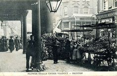 A busy Edwardian scene on Atlantic Road in Brixton, features several flower stalls trading under the viaduct that supports the northbound platform of Brixton Railway station.