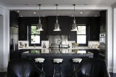 sleek, black kitchen. who would have known all black would look so nice. maybe with a purple or red dining space also with black accents?