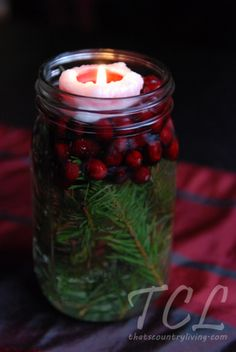 Simple and Pretty ~mason jar, greenery, cranberries, water, tea light~ simple Christmas table centerpiece done! :-) Idea from Better Homes and Gardens.