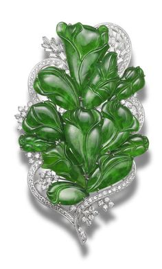 A jadeite and diamond brooch  Designed as a floral spray, set with intense green jadeite of very good translucency, carved as flowers, the largest measuring 30.6 x 21.9 x 2.8mm, highlighted with brilliant-cut diamonds, to stylised ribbons set with similarly-cut diamonds and baguette-cut diamond accents, mounted in 18k white gold, the diamonds estimated to weigh approximately 4.00 carats in total, brooch length 9.3cm