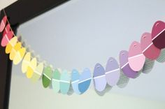 Paint Chip Easter Garland  Decorate your home with strings of rainbow colored Easter eggs made from paint chips! A great way for youngsters to practice their cutting skills.