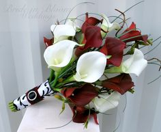 "This calla bridal bouquet is an elegant presentation style wedding bouquet. The callas lilies are soft to touch and look so real, you are sure to love them. There are 15 white & red mini calla lilies in this bouquet, added bear grass, vine and willow to make this a classy presentation ( one sided ) bouquet. Each lily bloom measures 2"" by 3"". Handle treatment is wrapped with satin ribbon and a damask overlay ribbon with a deep red velvet sash, completed with a sparkling rhinestone buckle…"
