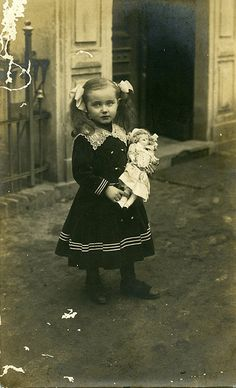 A little girl with long pony tails and hair ribbons standing in the street, in front of an open doorway, holds doll. Her dark dress is reminiscent of a sailor's suit with it's double row of buttons and pinstripes. A pointed lace collar makes the style more feminine.