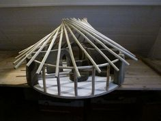Clay model of cob round house and reciprocal roof