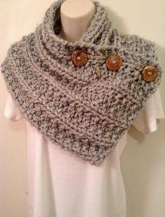 Cette écharpe chunky est élégant, doux et confortable. Il est tricoté à partir d'un fil de mélange acrylique/laine facile d'entretien et peut être porté avec un pull ou sous votre manteau d'hiver. Les boutons glissent à travers le tricot lâche afin que vous pouvez porter le foulard