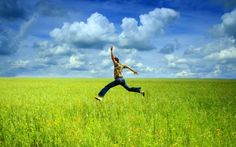 Man Jumps in Green Field Against Blue Sky