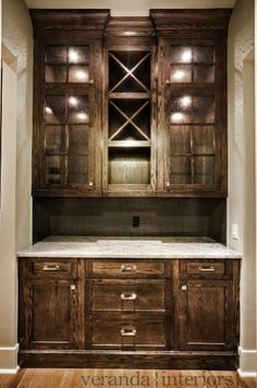 Gorgeous butler's pantry with coffee stained oak cabinets and stone countertops.