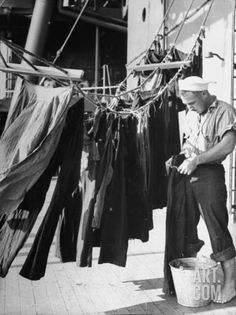 Sailor aboard a Us Navy Cruiser at sea hanging up laundered dungarees, WWII, by Ralph Morse