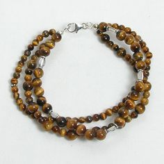 """Handmade gemstone tiger eye bracelet features 3 strands of semi-precious tiger eye gemstones, sterling silver beads, and lobster claw clasp. 8"""" in length. Add a necklace, pendant and earrings to compl"""