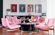 No espaço onde ficaria a mesa de jantar, a arquiteta Andrea Murao criou um lounge com mesa de centro baixa e aparador espelhado. A modernidade ficou por conta das cores usadas, como o rosa das cadeiras, os quadros e as caveiras